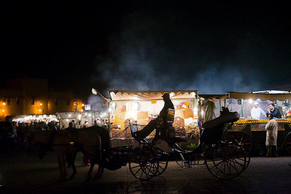 A man sits in a carriage in front of a market stall selling nuts and dried fruit on the Djemaa El-Fna square in the heart of the Marrakech medina, Morocco. The plaza bustles with food stalls and performers of all sorts till late every night.