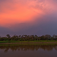 A sunset glows over the Amazon Jungle and Yanayacu River in Peru.