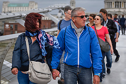 © Licensed to London News Pictures. 10/08/2019. LONDON, UK.  Tourists and Londoners cross the Millennium Bridge during windy conditions.  Much of the UK forecast to be subject to strong winds for the weekend.  Photo credit: Stephen Chung/LNP