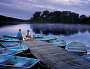 A father has a talk with his son at the end of a boat dock on a beautiful lake at sundown