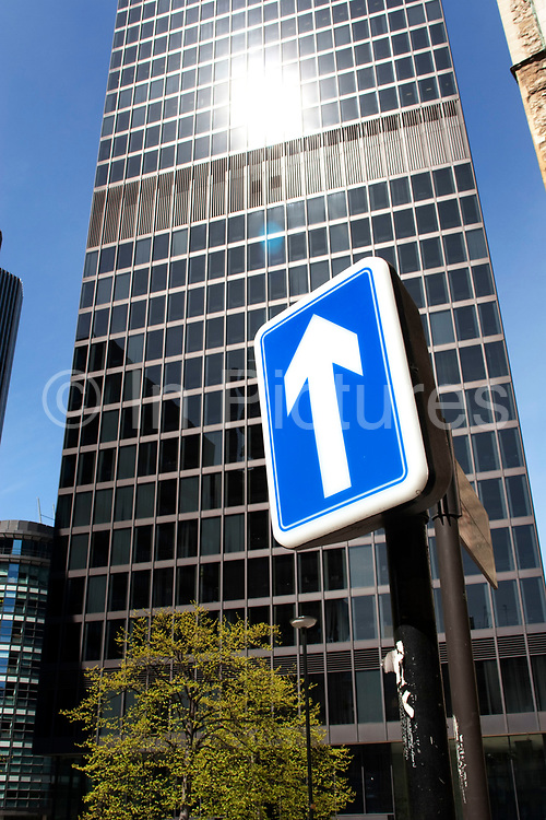 One way sign points to the sky near financial buildings in the City of London.