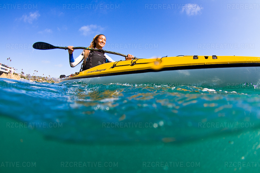Female kayaker paddling a Current Designs Vision 140 in the ocean.