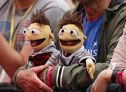 A festival goer carrying soft toy dolls whist watching Kris Kristofferson performing on the Pyramid Stage, at the Glastonbury Festival at Worthy Farm in Pilton, Somerset.
