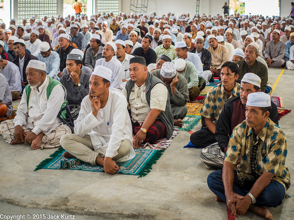 16 JUNE 2015 - CHANAE, NARATHIWAT, THAILAND:  Thai Muslim men listen to a local Imam during a prayer service in Chanae. About 600 people from Muslim communities in Chanae district of Narathiwat province came to the district offices Tuesday morning to participate in a prayer for peace during Ramadan. About 6,000 people have been killed in sectarian violence in Thailand's three southern provinces of Narathiwat, Pattani and Yala since a Muslim insurgency started in 2004. Attacks usually spike during religious holidays. Insurgents are fighting for more autonomy from the central government in Bangkok.       PHOTO BY JACK KURTZ