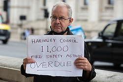 A man holds a sign referencing Haringey Council during a protest opposite Downing Street by leaseholders and tenants living in unsafe homes on 15th July 2021 in London, United Kingdom. Some leaseholders are faced with crippling costs to fix safety issues and they called on the government to ensure that their homes are made safe from fire as a matter of priority, to make interim payments and to cover fire safety remediation costs and to find a solution with mortgage lenders which enables them to move on with their lives.