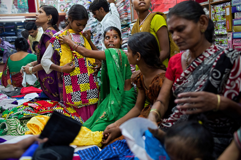 Sangita, 40, (centre) is checking the size of a new dress for her daughter Jyoti, 12, (left) while Poonam, 11, (right) is waiting for her turn, inside a local clothes shop in Bhopal, central India, near the abandoned Union Carbide (now DOW Chemical) industrial complex, site of the infamous '1984 Gas Disaster'.