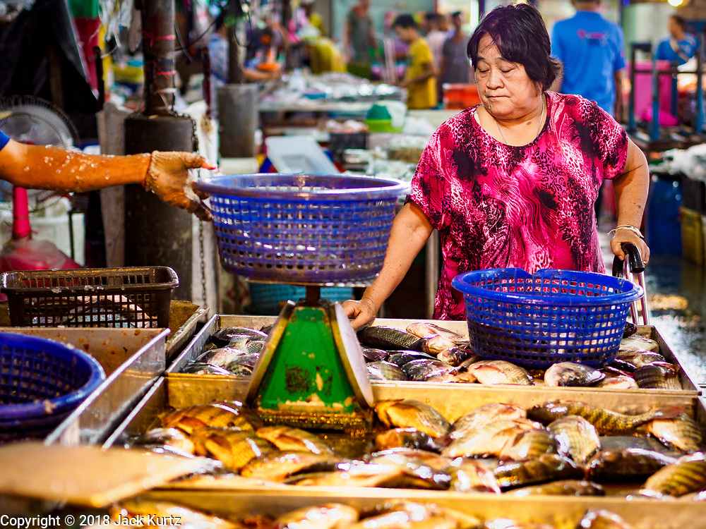 12 JULY 2018 - SAMUT PRAKAN, SAMUT PRAKAN, THAILAND: A consumer shops for fish in Pak Nam market in Samut Prakan. Fish consumption recently hit a record high according to a report published this week by the United Nations Food and Agriculture Organization. The FAO reported that global fish production peaked at about 171 million tonnes in 2016, 47 percent of it from fish farming. The FAO also reported that global fish consumption between 1961 and 2016 was rose nearly twice as fast as population growth. In 2015, fish accounted for about 17 percent of the animal protein consumed globally. This has ramifications for Thailand, which has one of the world's largest fish and seafood industries. About 90% of Thailand's seafood production is exported, which accounts for about 4% of Thailand's exports.    PHOTO BY JACK KURTZ