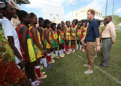Prince Harry meets the Grenada netball team during a community sports event at Queens Park Grounds in Grenada, during the second leg of his Caribbean tour.