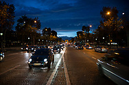Evening traffic drives on the Champs-Élysées, a boulevard in the 8th arrondissement of Paris, 1.9 kilometres long and 70 metres wide, which runs between the Place de la Concorde and the Place Charles de Gaulle, where the Arc de Triomphe is located. The Arc de Triomphe is visible in the distance.
