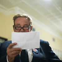 Hall Butchart looks over a set of unofficial voting results from the early voting and fire station polling places, Saturday at City Hall outside the Council Chambers.