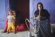 Hajja Sameeha smoking Shisha in her home, her daughter Mona and grandson Yaseen sitting with her, Gharb Aswan