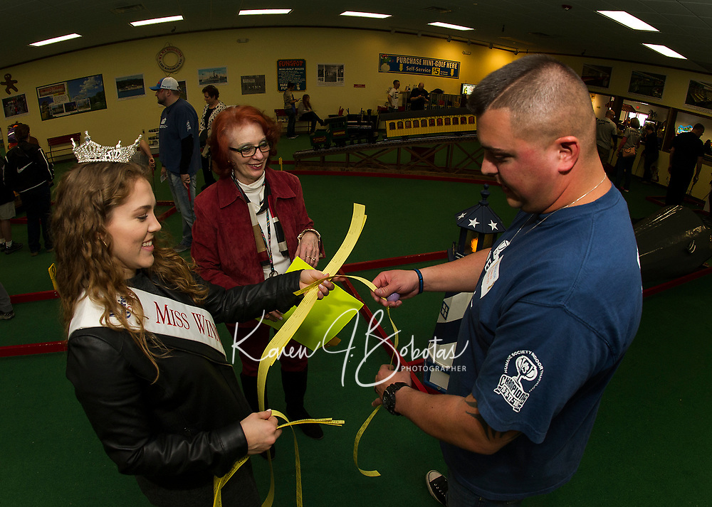Miss Winnipesaukee Brooke Mills and Tina Gebhard sell raffle tickets to Chris Heney of the Union Diner Dogs Team during the NH Humane Society Indoor Triathlon at Funspot on Saturday.  (Karen Bobotas/for the Laconia Daily Sun)