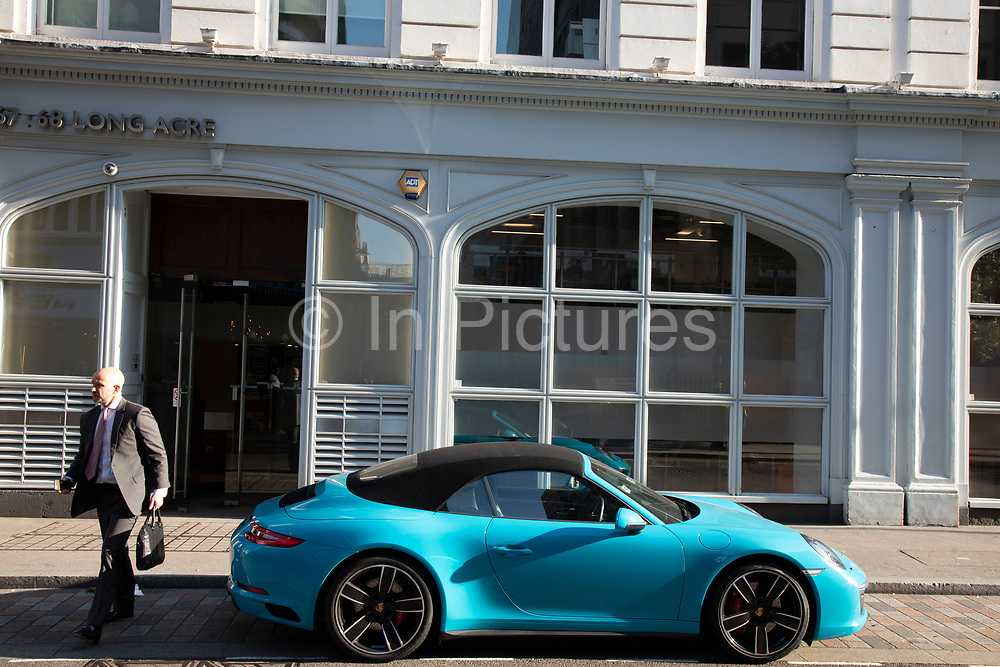Blue Porche supercar in London, United Kingdom. Dr.-Ing. h.c. F. Porsche AG, usually shortened to Porsche AG, is a German automobile manufacturer specializing in high-performance sports cars.