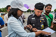 """24 JUNE 2014 - BANGKOK, THAILAND: A Thai police officer (right) talks to a poet  (left) about her poem after she read it aloud at a meeting of the Monsoon Poets Society in Bangkok. Members of the """"Monsoon Poets Society"""" gathered in front of the Anantasamakom Throne Hall Tuesday to pay homage to the People's Party, a Siamese (Thai) group of military and civil officers (which became a political party) that staged a bloodless coup against King Prajadhipok (Rama VII) and changed Thailand (then Siam) from an absolute monarchy to a constitutional monarchy on 24 June 1932. Since the coup against the civilian government on 22 May, the ruling junta has not allowed political gatherings. Although police read the poems, they did not arrest any of the poets or make any effort to break up the gathering.     PHOTO BY JACK KURTZ"""