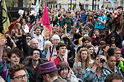 Climate change activists from the Extinction Rebellion group wait peacefully in the pavement as they wait an answer from Parliament to try deliver letters to their MPs at Parliament Square in protest that the government is not doing enough to avoid catastrophic climate change and to demand the government take radical action to save the planet, on 23rd April 2019 in London, England, United Kingdom. Extinction Rebellion is a climate change group started in 2018 and has gained a huge following of people committed to peaceful protests.