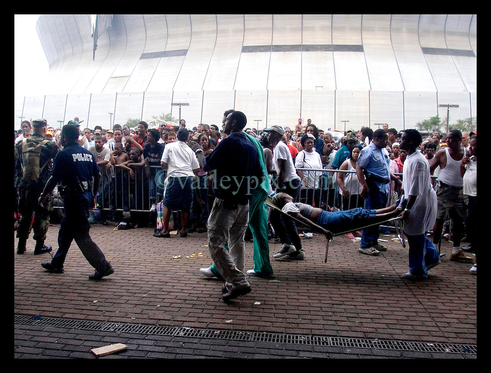1st Sept, 2005. Mass evacuation of New Orleans begins. Thousands of people mass at barriers awaiting instructions to board busses in a tense situation outside the Superdome. People collapsed and were carried away.