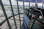 Aerial view (through control tower windows) showing NATS air traffic controllers and expanse of airport land at London Heathrow. Controlling aviation traffic on the ground and in the controlled airspace around London, the NATS controllers help safely guide up to 6,000 flights a day from the top of the 87 metre high tower, handling 1,350 aircraft movements a day into Heathrow.