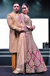 © Licensed to London News Pictures. 27/03/2016. Models on a catwalk stage wearing a groom suit and a bridal dress at the Asian Bride Live Wedding Show featuring fashion, beauty and services for brides to be. London, UK. Photo credit: Ray Tang/LNP