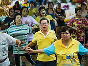 """21 DECEMBER 2015 - BANGKOK, THAILAND: People participate in an aerobics class in Pak Khlong Talat, also called the Flower Market. The market has been a Bangkok landmark for more than 50 years and is the largest wholesale flower market in Bangkok. Aerobics classes and fitness programs are common in Thai markets and parks. A recent renovation resulted in many stalls being closed to make room for chain restaurants to attract tourists. Now Bangkok city officials are threatening to evict sidewalk vendors who line the outside of the market. Evicting the sidewalk vendors is a part of a citywide effort to """"clean up"""" Bangkok.       PHOTO BY JACK KURTZ"""