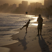 A late afternoon beach scene at Arpoador Beach as locals play football with Ipanema and Leblon in the distance. Rio de Janeiro, Brazil. 8th August 2010. Photo Tim Clayton...