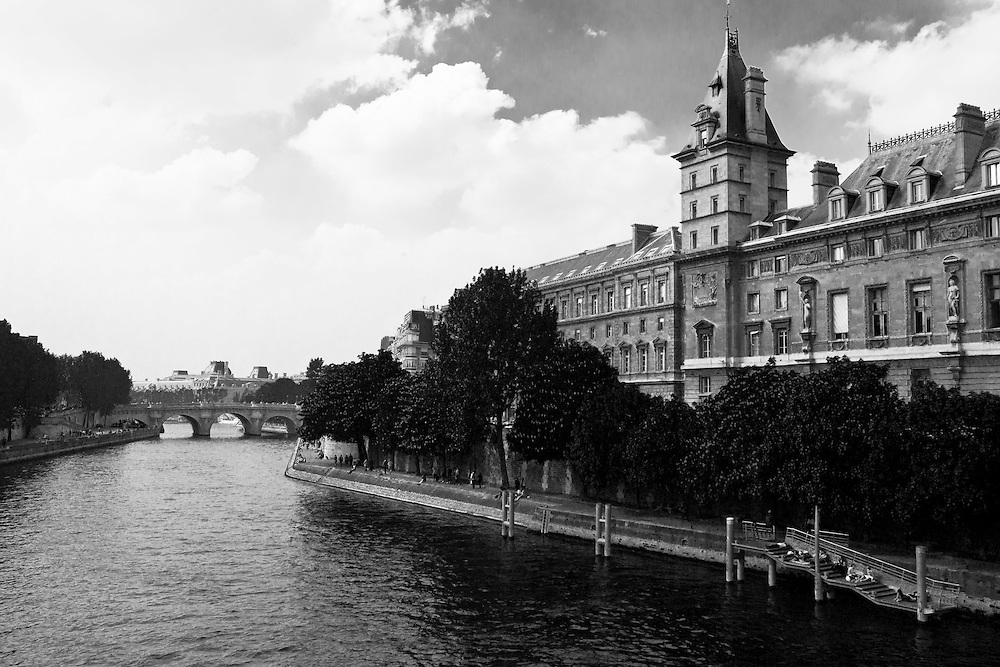 Palatial condominiums along the Westbank of the calm River Siene, Paris France in Europe. People stroll along the tree-lined walkway next to the river, Siene. A large stone bridge crosses bridge in the distance.