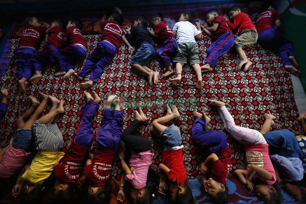 October 2, 2018 - Kathmandu, Nepal - Nepalese school children that are survivors from the victims of violence, abuse and poverty sleep at a kindergarten near a textile production center in Kathmandu, Nepal on Tuesday, October 2, 2018. The Production Center of Women's Foundation Nepal is situated in Boudha of the Capital.  There are more than 70 women aged above 45, who work to produce scarves, textiles and necklaces.  These women are producing and delivering around a total of 10-12kg materials per day.  Their basic income per month is between rupees 6,000-7,000 (Nepalese Currency) which comes around approximately 0-0. The handicrafts are sold in the center in a local price and are mainly exported to Europe, United States and Canada. The money from the exported items is used as charity to the women and children to cover all their basic needs, access provided to educational opportunities for the children, medical cost, psychological and legal assistance. The survivors of violence or abused children approximately 40-60 children aged 1-6 years go to kindergarten. Over 450 children from grade 1 to 10 studies at a school near Boudha.  The Women's Foundation Nepal also provides a safe shelter home for the young girls, boys and mothers. The shelter home has more than 120 children and 30 women and the above-mentioned expenditure is all funded by WFN. (Credit Image: © Skanda Gautam/ZUMA Wire)