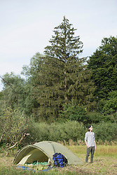 Teenage boy standing near his camp tent in forest, Bavaria, Germany