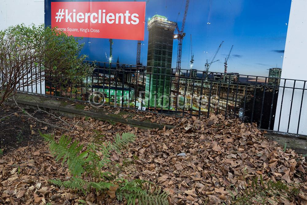 A construction hoarding from the contractor Keir and undergrowth of nearby church land, on 30th January 2018, in the south London borough of Southwark, England. Kier Group is a leading property, residential, construction and services group, employing over 21,000 people in its operations in the UK, the Middle East, Australia and Hong Kong.