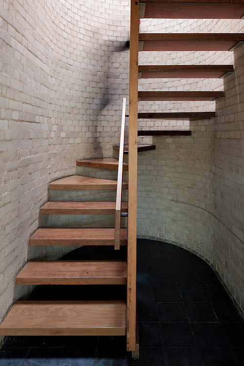 wooden 1960s staircase with grey brick walls with person walking down