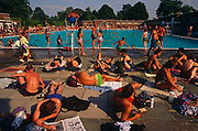 During an August heatwave, the population of Brixton and many others from all over London, bask in the glorious weather at the Brockwell (Brixton)  Lido in Brockwell Park, Herne Hill, South London. The Lido is a magnet for families, select groups, the young and old and represents an amalgam of humanity who enjoy the benefits of outdoor bathing and the friendship of meeting old friends and new acquaitances. We see a mass of people in late afternoon light with deep tans from the extended hot summer. There is little space left on the full pavement which retains its solar heat long after the sun has left the quadrangle of the lido's oblong design. They lay reading a newspaper or book, spread themselves on small towels or just chat to fellow-bathers. Swimmers are in the unheated water, others jump in or stand on the edge thinking about their next dive. It is a scene of chaotic fun for all ages and backgrounds. Brockwell Lido is a large, open air swimming pool in Brockwell Park, Herne Hill, London. It opened in July 1937, closed in 1990 and after a local campaign was re-opened in 1994. Brockwell Lido was designed by HA Rowbotham and TL Smithson of the London County Council's Parks Department to replace Brockwell Park bathing pond. It is now a Grade II listed building