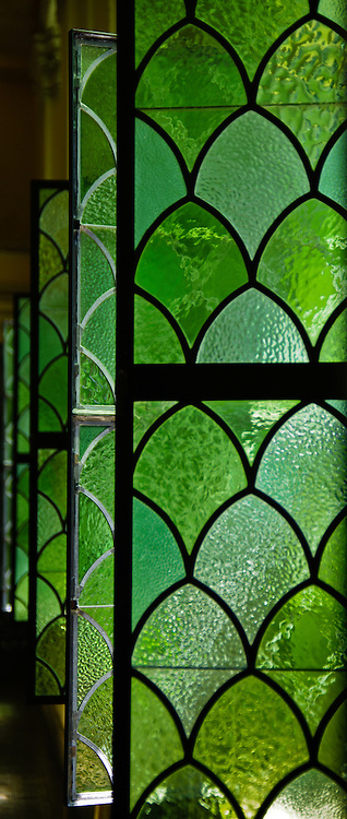 The ornate pool at the Intercontinental Hotel on Chicago's Magnificent Mile is accented with luxurious architectural details such as sconces, decorative textured green glass windows, stadium seating with green and beige rattan furnishings.