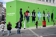Shoppers cross the road towards the temporary hoarding for Balenciaga, a retail space which is opening soon on Bond Street, on 27th April 2021, in London, England. Balenciaga is a fashion house founded in 1917 by Spanish designer Cristóbal Balenciaga in San Sebastián, Spain.