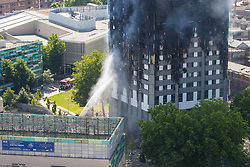 London, June 14th 2017. A fire rages through a residential tower block, Grenfell Tower, in Kensington, West London, with the entire building engulfed in flames. More than 200 firefighters are attending the incident and there are reports of people trapped inside. No figures are available as to casualties. PICTURED: The lower floors appear to have suffered less damage, probably due to the fact that firefighters are able to train their water jets on them.