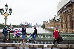 London, UK. 19 July, 2019. Tourists with umbrellas brave heavy rain showers on Westminster bridge.