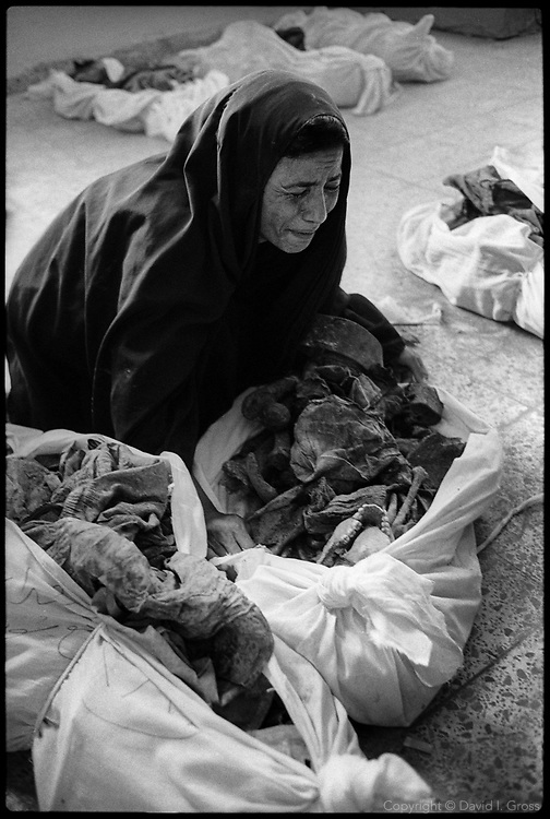 A woman cries in frustration while searching for her missing relatives among the bones in shrouds that fill the gymnasium of the local sports center in Al-Musayab, Iraq. People come from all over to check the clothing and ID cards of the bodies, looking for long-lost relatives.