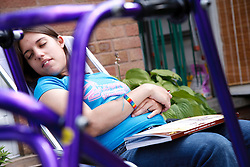 Young woman with Cerebral Palsy who uses a walking frame asleep in garden.