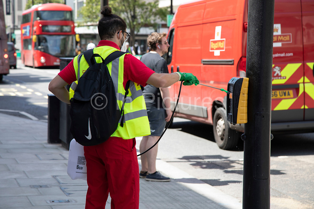 Worker disinfects the areas which people regulalrly touch with their hands along Oxford Street as the Coronavirus lockdown measures are set to ease further, the west end starts to fill with people as they return to the shopping district and the quiet city starts coming to an end on 22nd June 2020 in London, England, United Kingdom. As of today the government has relaxed its lockdown rules, and is allowing some non-essential shops to open with individual shops setting up social distancing queueing systems.