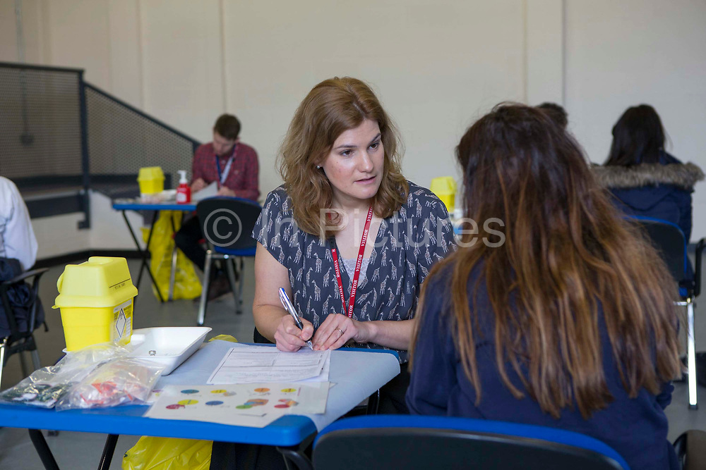 Sarah Murphy, TB Nurse Specialist for Public Health England's London TB Extended Contact Tracing Team (LTBEx) whilst doing a health assessment on a teenage school girl as part of tuberculosis contact screening in a community secondary school in London. UK