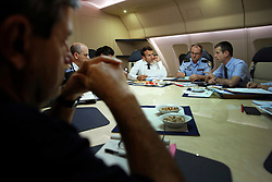 France's President Emmanuel Macron, center, confers with officials aboard the presidential plane en route to Guadeloupe Island, the first step of his visit to French Caribbean islands, Tuesday, Sept. 12, 2017. Seated at the table are director general of the Gendarmerie Nationale, Richard Lizurey, 2nd right, and director of the rescue service (Securite Civile), Jacques Witkowski, 2nd right. Photo by Christophe Ena/Pool/ABACAPRESS.COM
