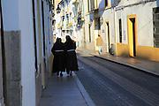 Two nuns walking together along pavement, Cordoba, Spain