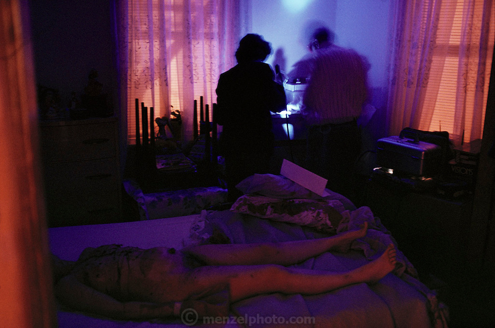 "(1992) NYPD Crime Scene Unit responding to a possible homicide/rape of a 49-year-old white woman in her apartment in Flushing, New York. She was attacked in the kitchen, carried into the bedroom, tied and then stabbed 31 times. Detective Arnie Roussine and Kim Geis are seen using a forensic laser ""Omniprint 1000"" to look for traces of sperm on the bloody sheets at the foot of the bed. Roussine has served 28 years with the Crime Scene Unit---he has worked on 7,000 cases (3,000 of them have been homicides.) DNA Fingerprinting.."