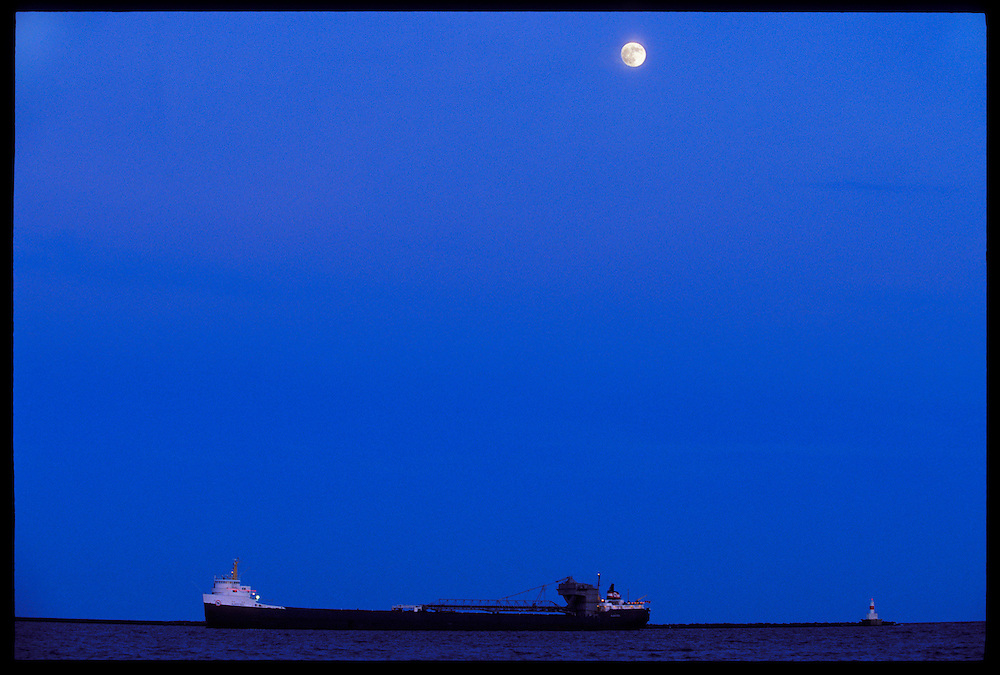 THE FREIGHTER ALGOSTEEL UNDER A FULL MOON WITH MARQUETTE'S UPPER HARBOR BREAKWATER LIGHT IN MARQUETTE MICHIGAN.