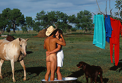 naked cowboy and girl in a towel kissing while in an outdoor metal bathtub while a horse and dog look on