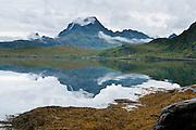 A mountain on Moskenesøya (the Moskenes Island) reflects in Torsfjorden in the Lofoten archipelago, Nordland county, Norway.