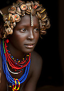 "Ethiopian Tribe Recycles Modern World's Discards Into Fashion Accessories<br /> <br /> The Daasanach are a semi-nomadic tribe numbering approximately 50,000 individuals who live in the Omo Valley in southern Ethiopia. In the past, the tribe roamed from place to place herding livestock around open areas according to the seasons and the changing availability of water. But over the last fifty years, having lost the majority of their lands, they have also grown dependent to agriculture. Like many tribes in the region, the Daasanach have moved to areas closer to the Omo River, where they attempt to grow enough crops to survive.<br /> <br /> French photographer Eric Lafforgue has spent several years documenting the life and culture of these people, and how they have changed under the influence of modern manufactured goods. An interesting fashion trend amongst the Dassanach is their elaborate headgear, which they make from the strangest of materials — bottle caps, wristwatches, hairclips, and other discarded pieces of plastic and metal.<br /> The Daasanach spend months collecting bottle caps and scratching around for cash to pay for broken watches, which the women makes into jewelry and wigs. These are worn by both men and women, young and old.<br /> <br /> ""Younger girls and children get the most basic version of the wig, while the oldest women are treated to the heaviest numbers with the most embellishment,"" wrote The Daily Mail. ""Men are only allowed to wear the bottle top wigs until they marry - after that, they create small clay headpieces decorated with a colourful harlequin pattern and enlivened with a feather, although the latter is only allowed after a hunt or a successful clash with an enemy.""<br /> <br /> ""The young men love to wear necklaces and earrings while the girls have bigger muscles because they do the most difficult work like carrying water,"" Eric Lafforgue told the newspaper.<br /> <br /> To prevent their headgears from getting spoiled while they sleep (apparently, they never take them off), they use"