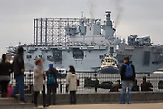 HMS Ocean of the Royal Navy edges upstream on the River Thames towards Greenwich ahead of a major security exercise in preparation for the 2012 Olympic Games. Ocean is an amphibious assault ship (or landing platform helicopter), the sole member of her class and the Royal Navy's largest ship, here to act as a launch pad for eight army Lynx helicopters and a base for Royal Marine snipers, able to shoot at the engines of fast-moving targets. It is the final phase of the exercise named Olympic Guardian, which began on the coast and in the airspace over the capital. During the Olympics, Ocean will be moored in Greenwich to provide logistics support, accommodation to 9 Assault Squadron Royal Marines and a helicopter landing site. The 203.4m (667 ft) long, 21,500 tonnes Ocean was constructed in the mid 90s at a cost of £234 million.