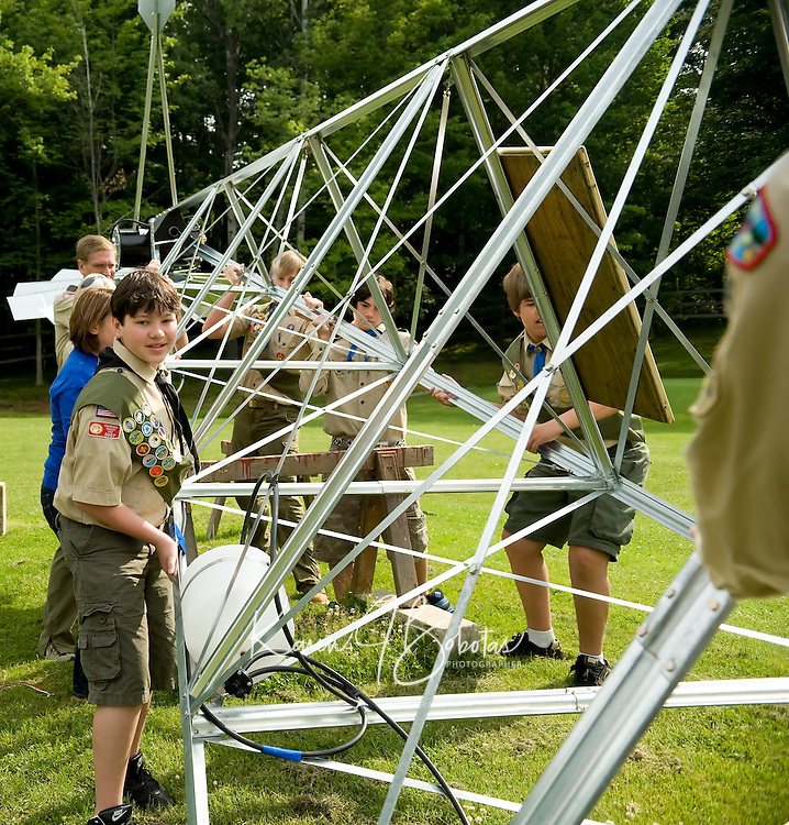 15 year old Eagle Scout candidate Cameron Skarritt hoists the windmill he built for his Eagle project to pump oxygen into the pond at Bolduc Park along with his brother Connor and fellow scouts on Saturday morning.  (Karen Bobotas/for the Laconia Daily Sun).