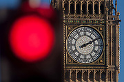 A red traffic light in the foreground and the clockface containing the Big Ben bell in the Elizabeth Tower of the British parliament, on 17th January 2017, in London England.