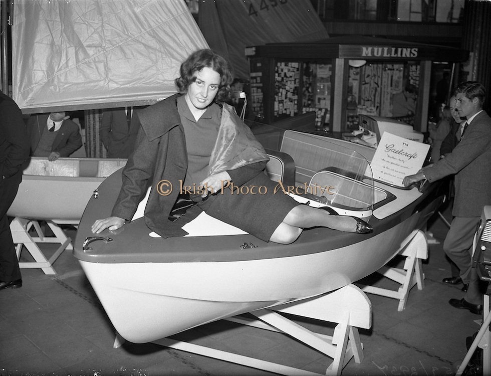 """18/04/1960<br /> 04/18/1960<br /> 18 April 1960<br /> The First Annual Boat Show at  Busaras, Store Street, Dublin.<br /> Just trying it for size is Miss Pasquelle Farrell, Stepaside, Co. Dublin, a maid of the mountains who's thoughts are turning to the seas. """"We found Pasquelle picking a boat for herself at the first National Boat Show which opened in Dublin on Easter Monday. She hopes to join the sport this season"""" original caption."""