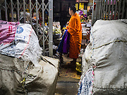 "21 DECEMBER 2015 - BANGKOK, THAILAND:  Buddhist monks collect alms from a shopkeeper in Pak Khlong Talat, also called the Flower Market. The market has been a Bangkok landmark for more than 50 years and is the largest wholesale flower market in Bangkok. A recent renovation resulted in many stalls being closed to make room for chain restaurants to attract tourists. Now Bangkok city officials are threatening to evict sidewalk vendors who line the outside of the market. Evicting the sidewalk vendors is a part of a citywide effort to ""clean up"" Bangkok.      PHOTO BY JACK KURTZ"
